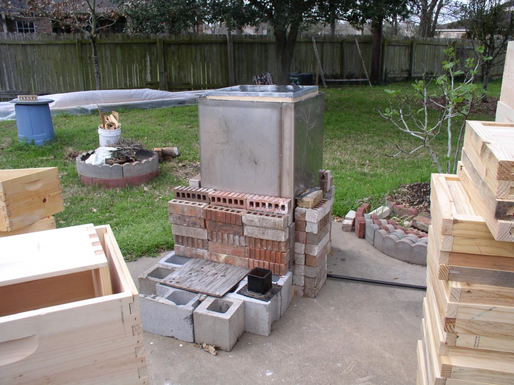 Here's the stainless steel tank surrounded by a double layer of bricks to help conserve the heat.  The cinder blocks are to stand on to reach down and get the woodenware out of the tank when the process is completed.